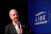 Foto com a imagem do economista Marcelo Neri no evento e ao fundo a logo do LIDE - Grupo de Líderes Empresariais